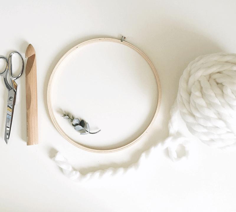 DIY modern Christmas wreath made with an embroidery hoop, jumbo yarn, and a crochet hook.