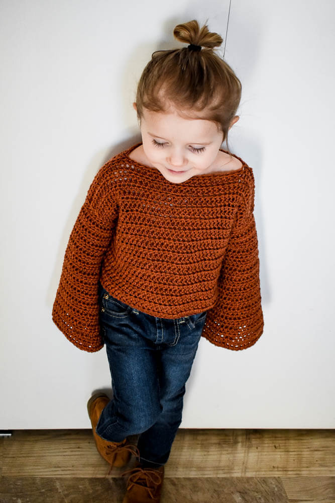 a crochet toddler sweater in a rich rust color. Perfect free crochet pattern for beginners. I love the flare sleeves.