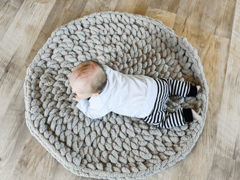 A free crochet pattern for a baby play mat that uses chunky yarn. This plush play mat will make a great baby gift.