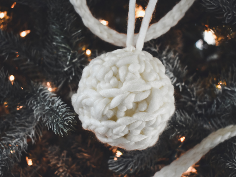 White crochet Christmas ornament on a Christmas tree.