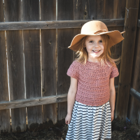 toddler girl wearing a crocheted crop top over a striped dress