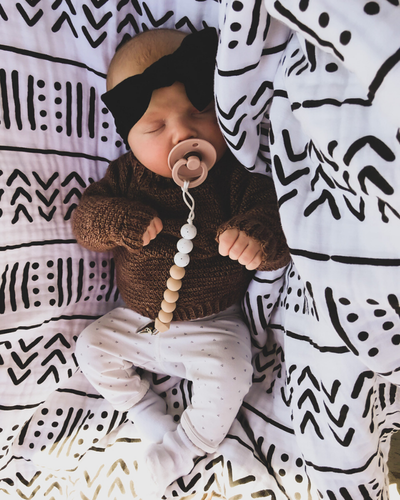 A sleeping baby wearing a handmade crocheted sweater. Get the free crochet pattern.
