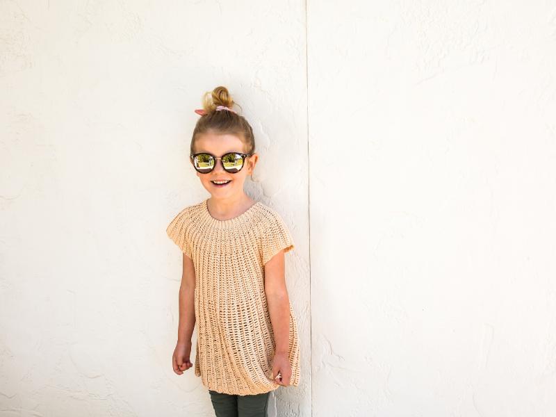 a little girl wearing her summer tunic crochet pattern in beige